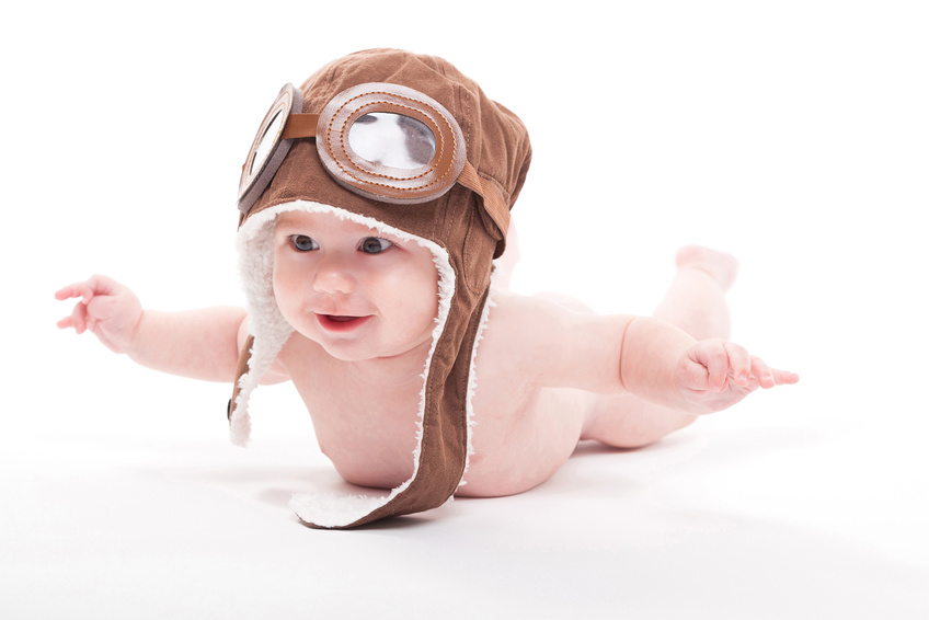 cute smiling baby in the cap of the pilot is flying on a white background. Photo with artistic blur and depth of field